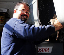 Mechanic Domenic from Sam's Service Centre smiles as he does some brake repair