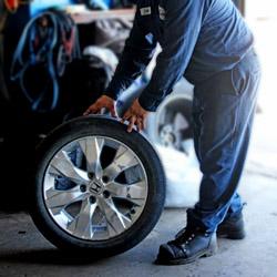 Paul rolling a Honda tire across the floor  of the garage floor at Sam's